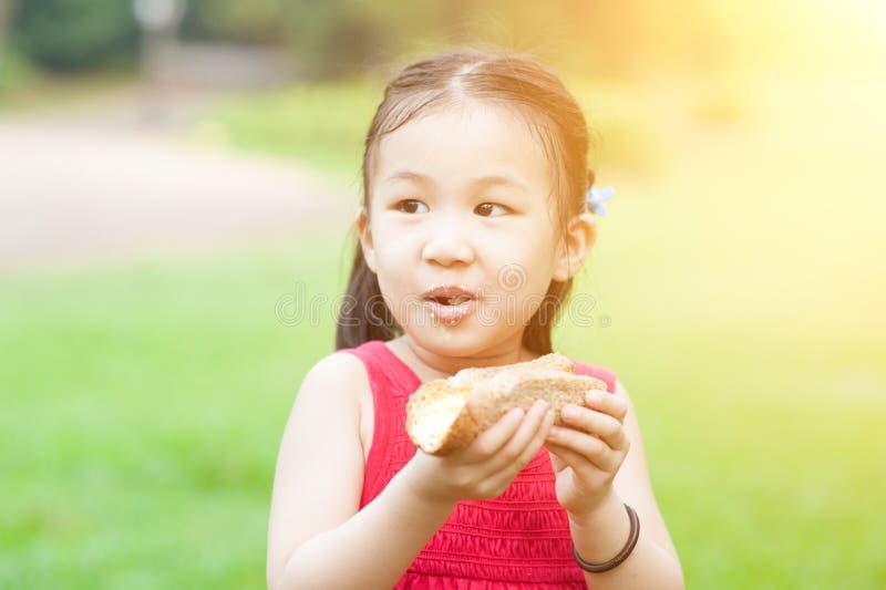 Asiatisches Kind, das draußen isst stockbilder