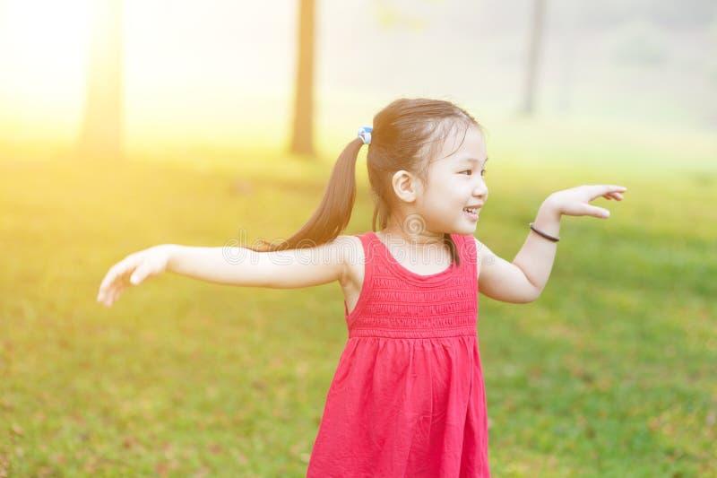 Asiatisches Kind, das draußen tanzt lizenzfreies stockfoto