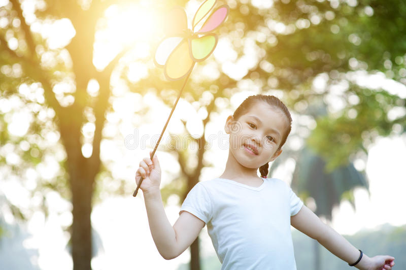 Asiatisches Kind, das draußen Windmühle spielt stockfotografie