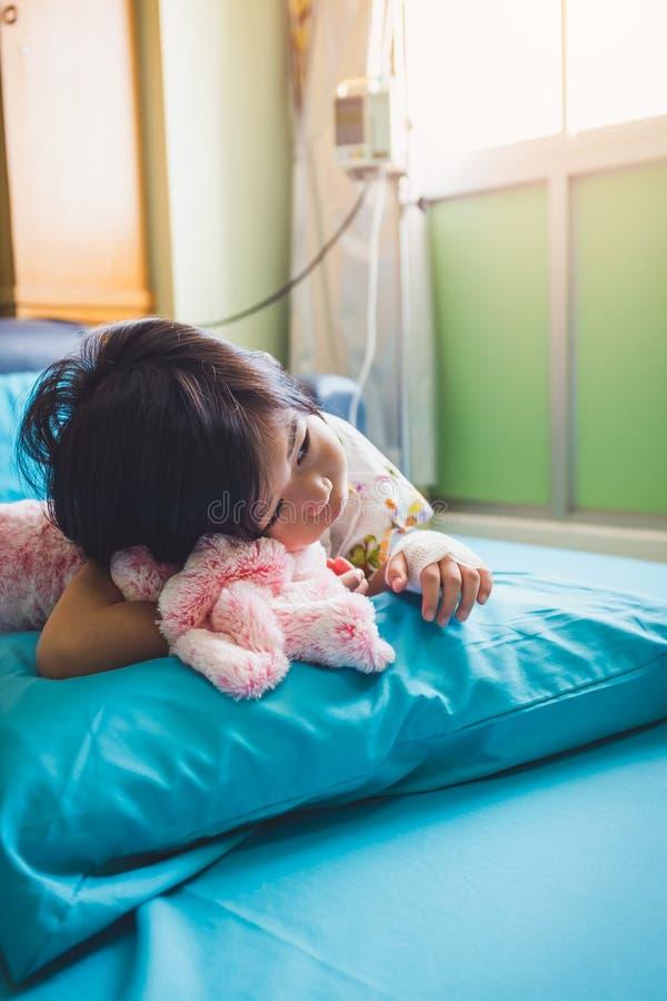 Asiatisches Kind der Krankheit lie? im Krankenhaus mit salzigem iv-Tropfenf?nger an Hand zu Gesundheitswesengeschichten stockbilder