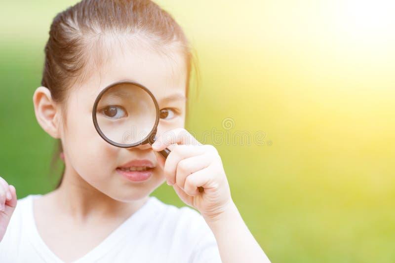 Asiatisches Kind mit Vergrößerungsglasglas an draußen stockbilder