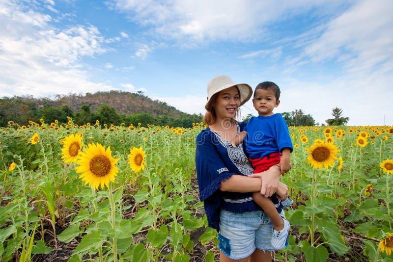 Asiatisches Kind oder Baby und glückliche junge Mutter in der Sonnenblumenwiese stockfoto