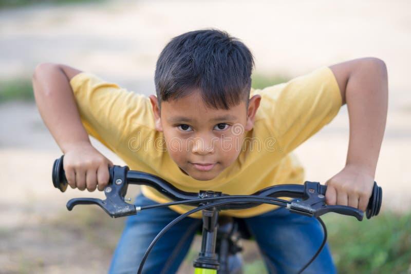 Asiatisches Kinderjungen-Fahrfahrrad in der Natur lizenzfreie stockbilder