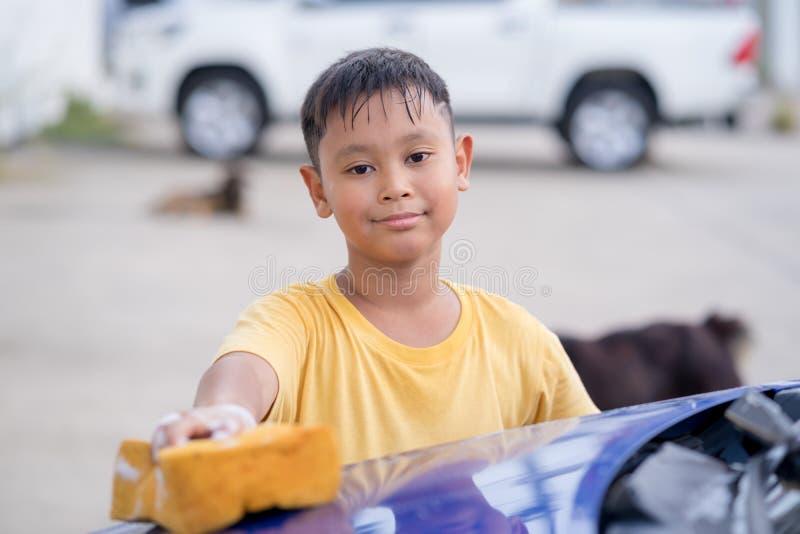 Asiatisches Kinderjungen-Reinigungsauto stockfotos