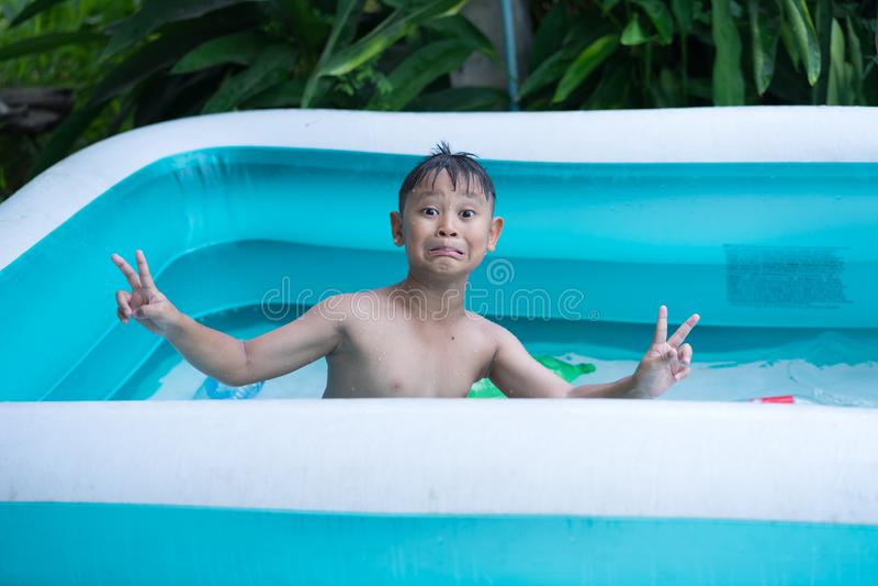 Asiatisches Kinderjungen-Spielwasser im aufblasbaren Swimmingpool stockbilder