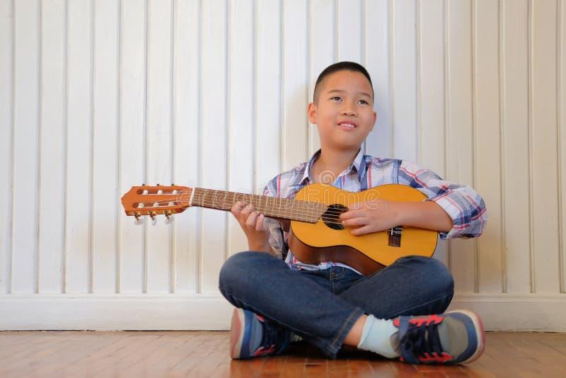 asiatisches Kinderjungenkind, das Gitarrenukulele spielt Kinderfreizeittat stockbilder