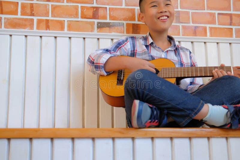 asiatisches Kinderjungenkind, das Gitarrenukulele spielt Kinderfreizeittat lizenzfreies stockbild