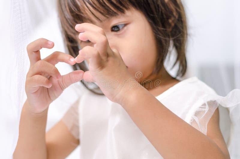 Asiatisches Kinderkleinkindmädchen, das Liebesherzzeichen durch ihre Hand macht stockbild