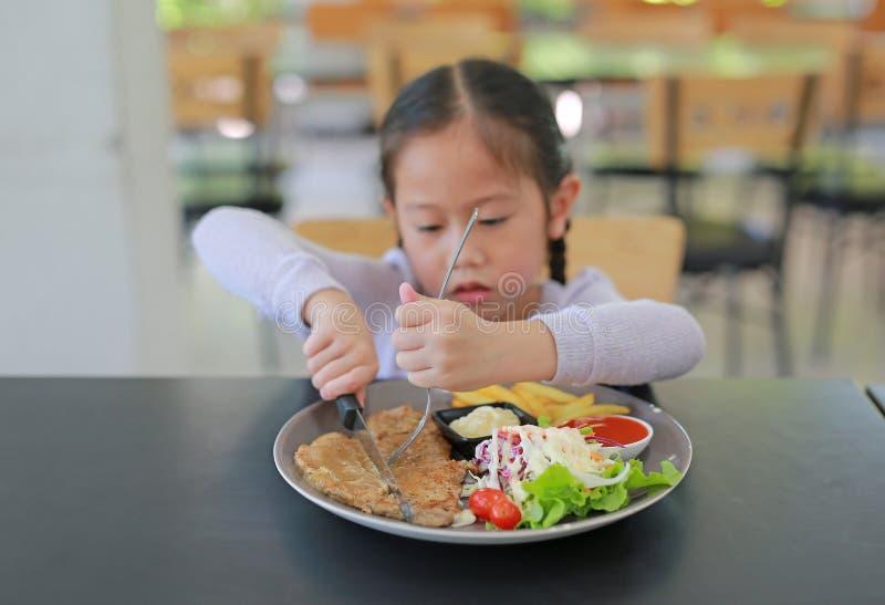 Asiatisches Kindermädchen, das auf dem Tisch Schweinefleischsteak und Gemüsesalat mit Holdingmesser und -gabel isst Kinder, die f lizenzfreie stockfotos