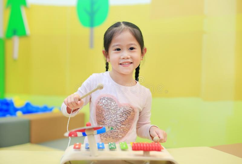 Asiatisches Kindermädchen, das Spaß mit Spielwaren, Musikinstrumente hat stockbild