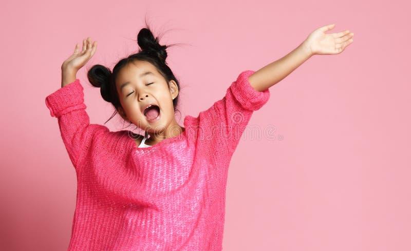 Asiatisches Kindermädchen in der rosa Strickjacke, in den weißen Hosen und in den lustigen Brötchen singt Gesangtanzen auf Rosa lizenzfreie stockfotografie