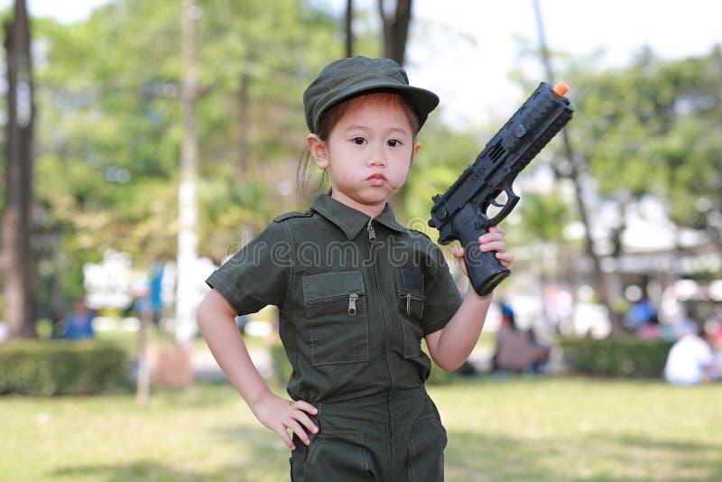 Asiatisches Kindermädchen im Versuchssoldatklagenkostüm mit schießendem Gewehr oben Traumjobkonzept lizenzfreies stockfoto