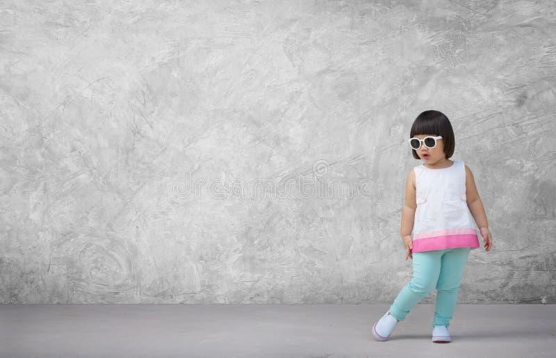 Asiatisches Kindermädchen mit Betonmauerhintergrund im leeren Raum stockbild