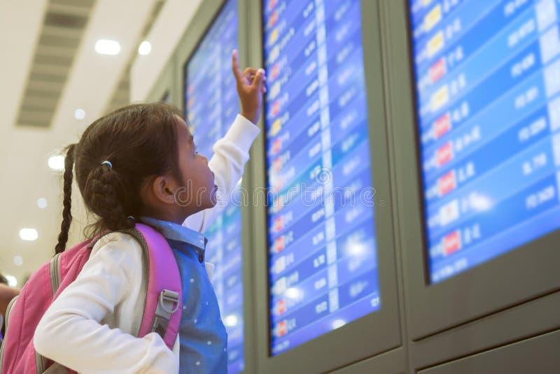 Asiatisches Kindermädchen mit Rucksack ihren Flug am Informationsbrett im internationalen Flughafenabfertigungsgebäude überprüfen stockbild