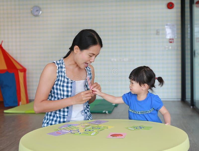 Asiatisches Kindermädchen und -mutter, die Flash-Karte für rechten Brain Development am Spielzimmer spielt lizenzfreie stockfotos