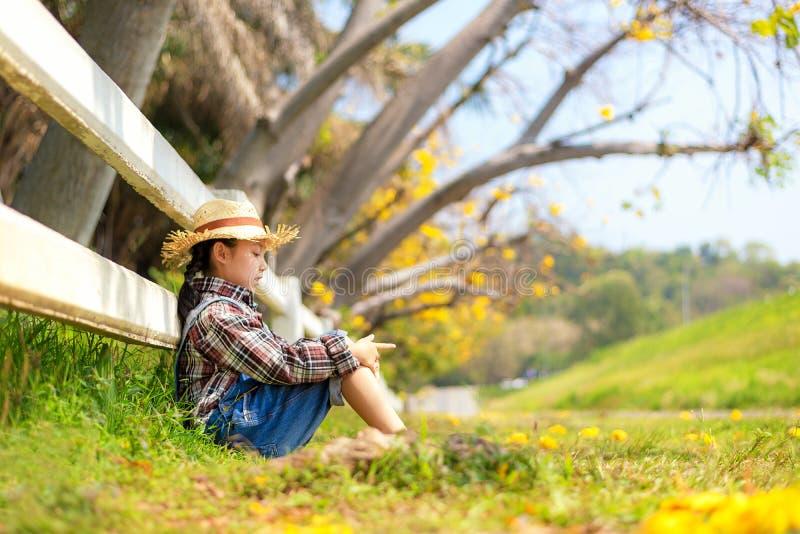 Asiatisches Kindermädchensitzen im Freien in gefallenen Blättern am Herbst im Park, glücklich und in der Sommerzeit sich entspann lizenzfreie stockfotografie