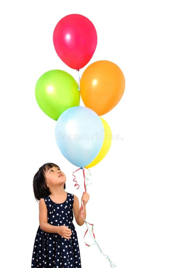 Asiatisches kleines chinesisches Mädchen, das bunte Ballone hält lizenzfreie stockfotos