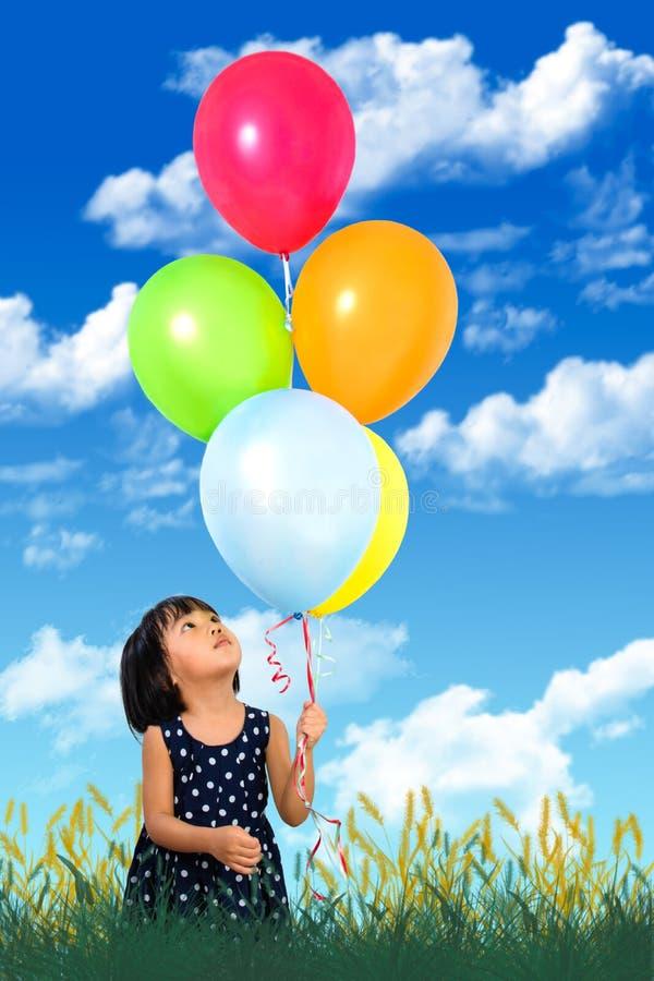 Asiatisches kleines chinesisches Mädchen, das bunte Ballone hält lizenzfreie stockbilder