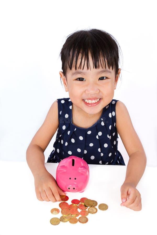 Asiatisches kleines chinesisches Mädchen-Einsparungs-Geld in einem Sparschwein stockfoto