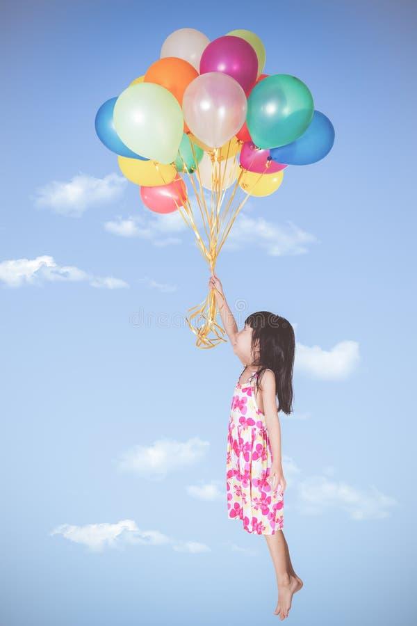 Asiatisches kleines chinesisches Mädchenfliegen mit bunten Ballonen lizenzfreie stockfotografie