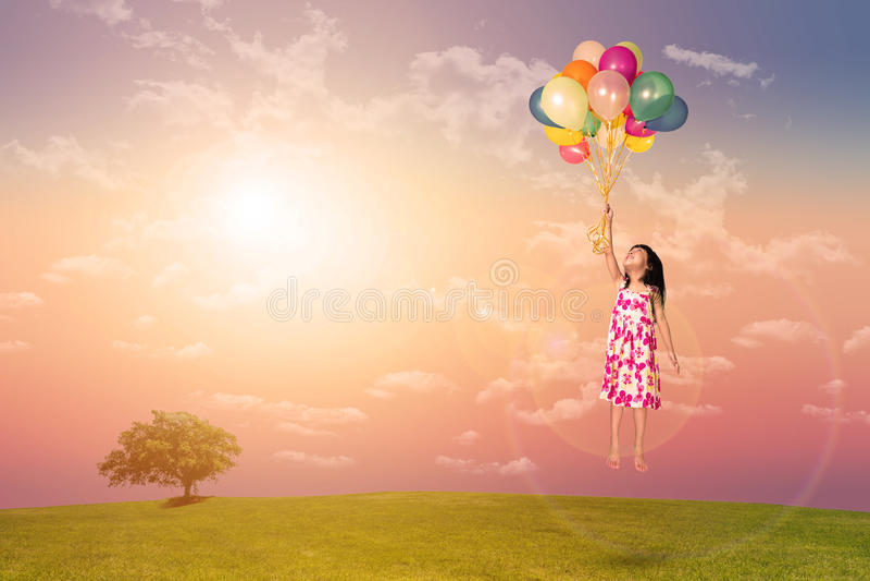 Asiatisches kleines chinesisches Mädchenfliegen mit bunten Ballonen lizenzfreies stockbild