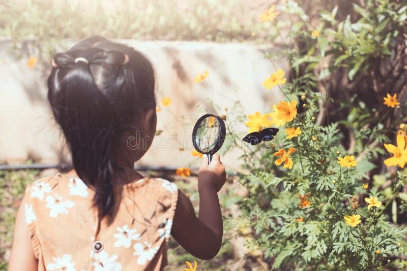 Asiatisches kleines Kindermädchen, das aufpassenden Schmetterling der Lupe verwendet stockfoto