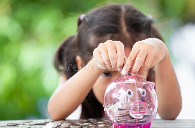 Asiatisches kleines Kindermädchen, das Geld in Sparschwein steckt stockfotos