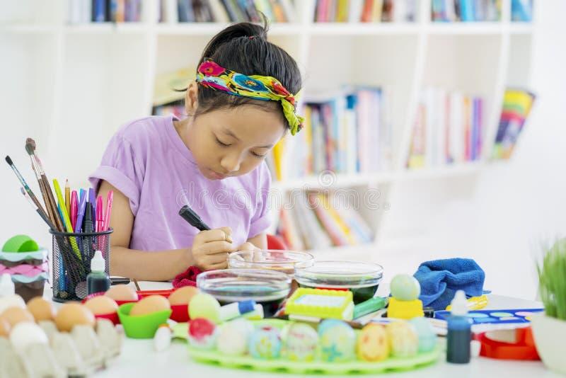 Asiatisches kleines Mädchen, das lernt, Ostereier zu malen lizenzfreie stockbilder