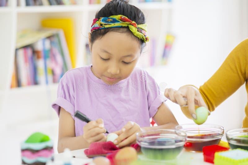 Asiatisches kleines Mädchen lernt, Eier mit ihrer Mutter zu färben lizenzfreie stockfotografie