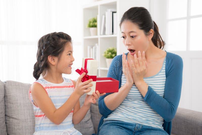 Asiatisches kleines Mädchen, das Geschenk rote Bandgeschenkbox schickt stockbilder