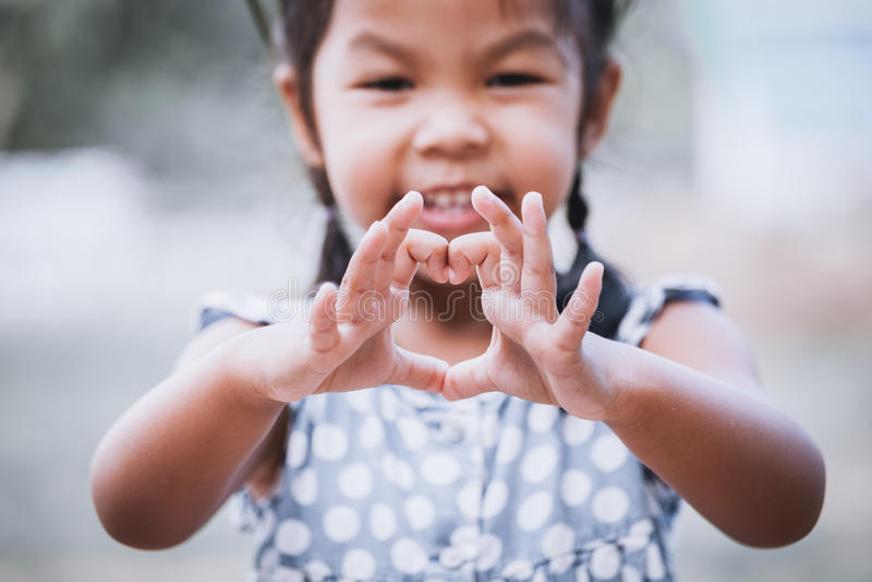 Asiatisches kleines Mädchen, das Herzform mit den Händen macht lizenzfreie stockbilder