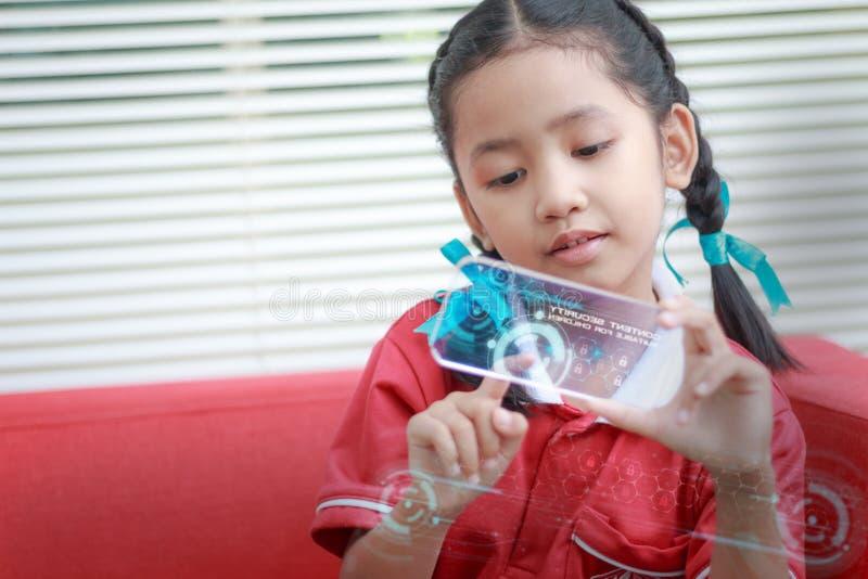 Asiatisches kleines Mädchen, das intelligentes Mobiltelefon mit HUD-Kopf herauf DISP verwendet lizenzfreies stockbild