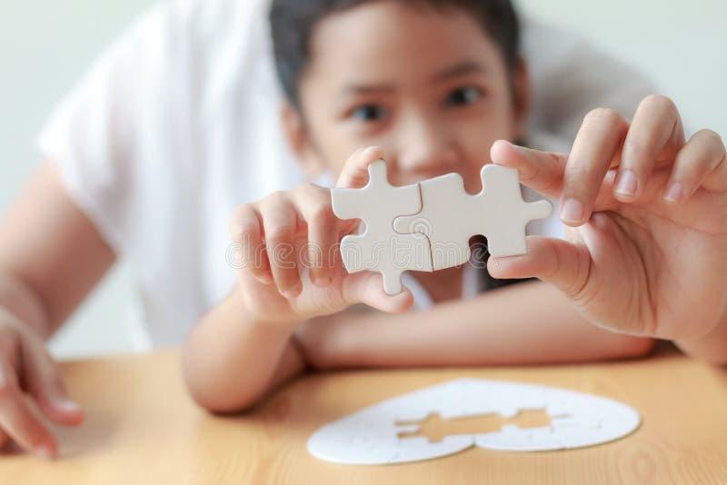 Asiatisches kleines Mädchen, das Puzzlen mit ihrer Mutter für fami spielt lizenzfreie stockfotos