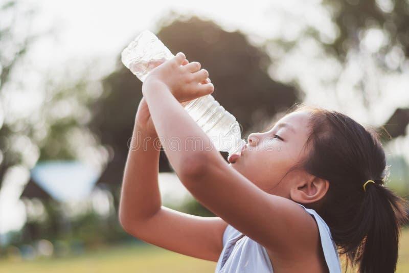 asiatisches kleines Mädchen, das Süßwasser von der Plastikflasche mit trinkt stockfotografie