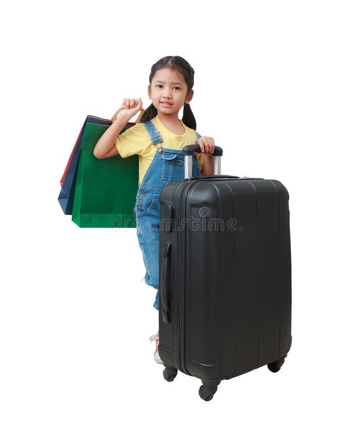 Asiatisches kleines Mädchen des Lächelns, das Einkaufstasche und Gepäck mit ha hält lizenzfreie stockbilder