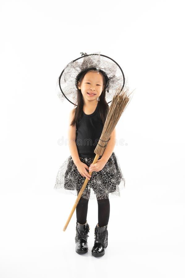 Asiatisches kleines Mädchen des Porträts, das in der netten Hexe für Halloween ankleidet lizenzfreie stockbilder