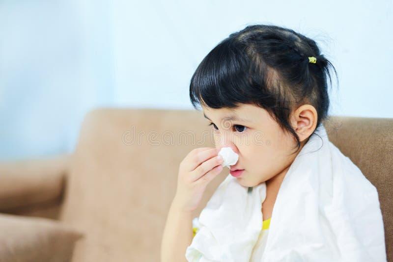 Asiatisches kleines Mädchen krank in Taschentuch eingepackt bekommen kalt und blasen die Grippesaison nasen und niesen sie ihre G lizenzfreie stockfotografie