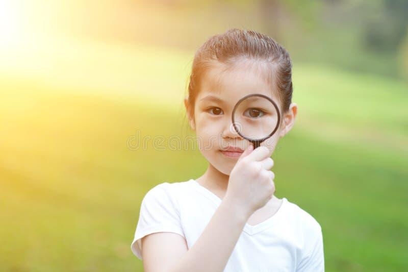 Asiatisches kleines Mädchen mit Vergrößerungsglasglas an draußen stockfotos