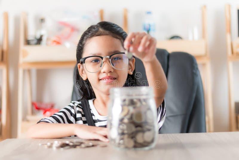 Asiatisches kleines Mädchen, wenn herein Münze zum Glasgefäß für Einsparung Montag gesetzt wird lizenzfreie stockfotos