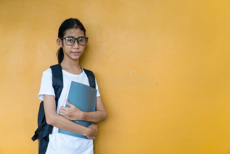Asiatisches kleines Schulmädchen mit Rucksackholdingbuch stockbilder