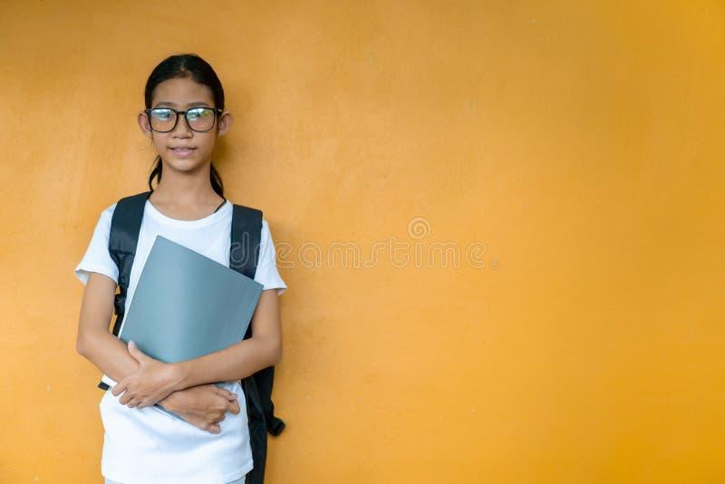 Asiatisches kleines Schulmädchen mit Rucksackholdingbuch stockfotografie