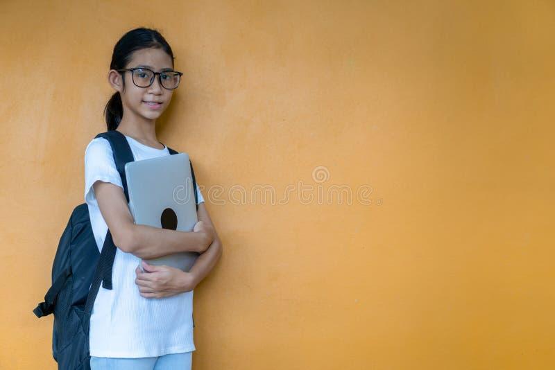 Asiatisches kleines Schulmädchen mit Rucksackholdinglaptop lizenzfreies stockfoto