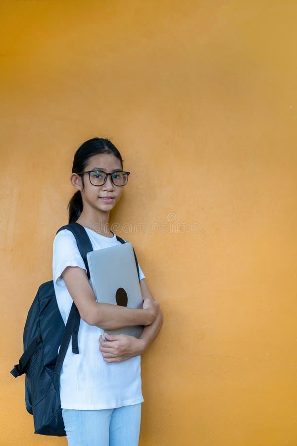 Asiatisches kleines Schulmädchen mit Rucksackholdinglaptop lizenzfreie stockbilder