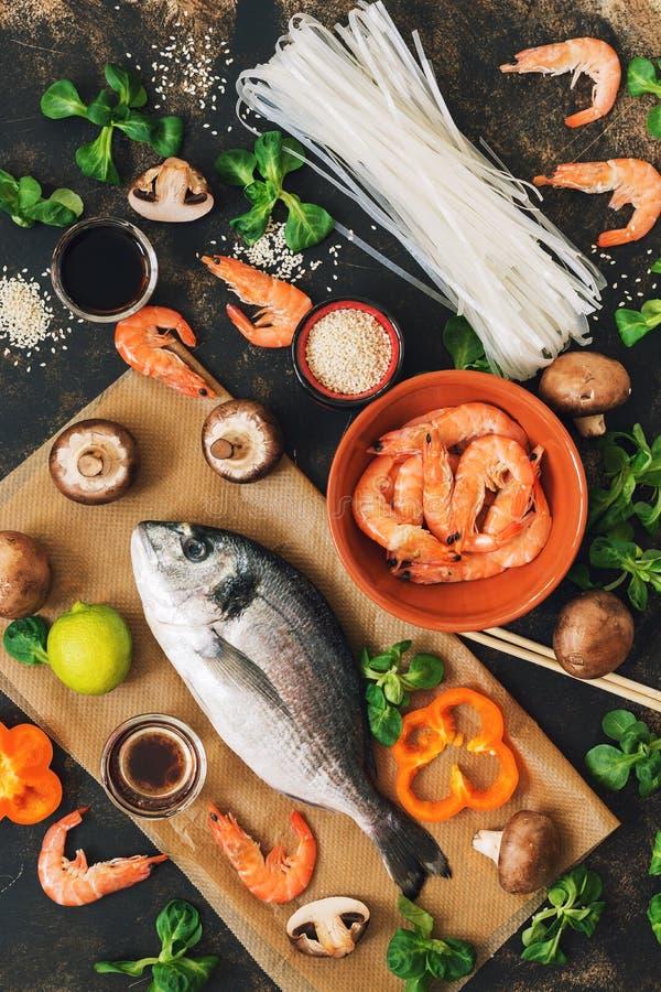 Asiatisches Lebensmittel auf rustikalem Hintergrund Reisnudeln, rohe Fische, Pilze und Garnelen Die Ansicht von der Oberseite lizenzfreie stockfotografie