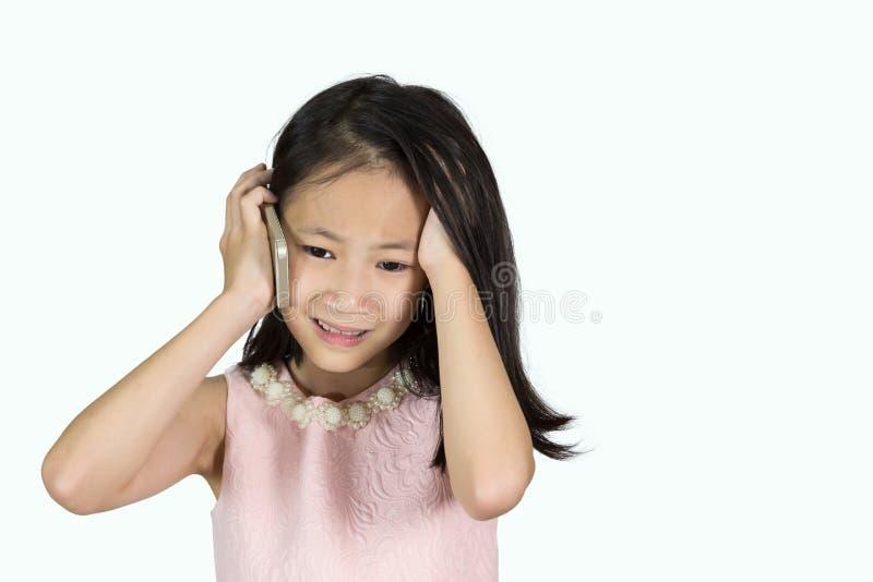 Asiatisches Mädchen benutzt einen Handy, der auf weißem Hintergrund, der Druck lokalisiert wird, traurig lizenzfreie stockfotografie