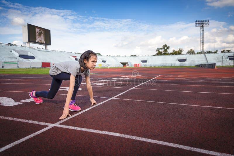 Asiatisches Mädchen bereiten vor sich, in den Ausgangspunkt an der Rennbahn, am Betrieb und an der Übung für Gesundheit zu laufen lizenzfreie stockbilder