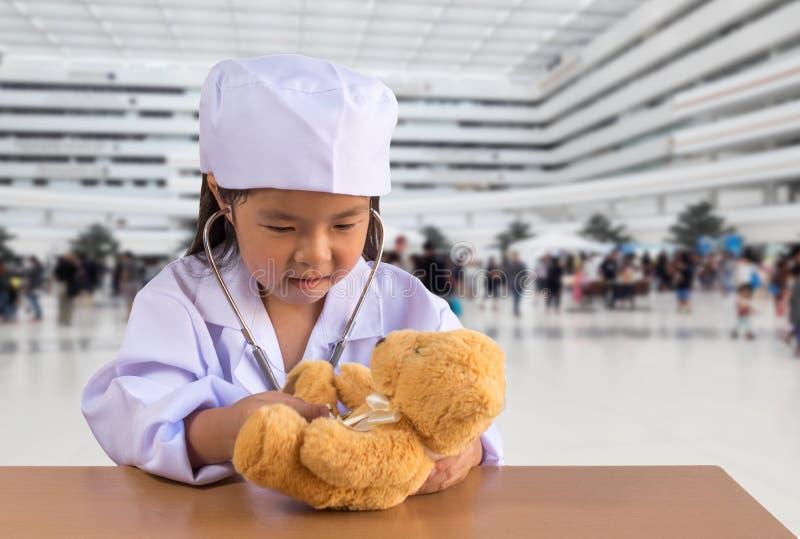 Asiatisches Mädchen, das als Doktorsorgfalt-Bärnpuppe spielt lizenzfreies stockbild