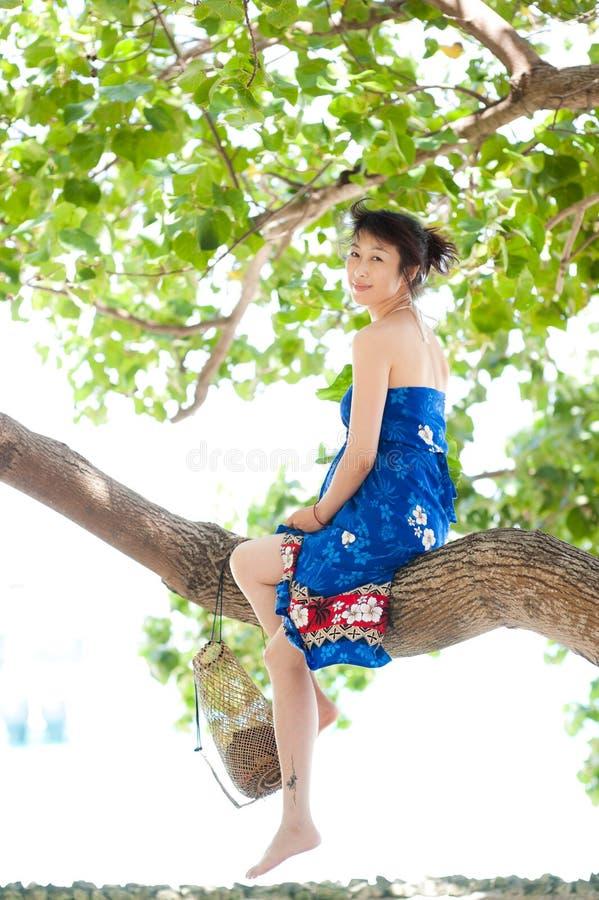 Asiatisches Mädchen, das auf Baumkabel sitzt lizenzfreies stockfoto