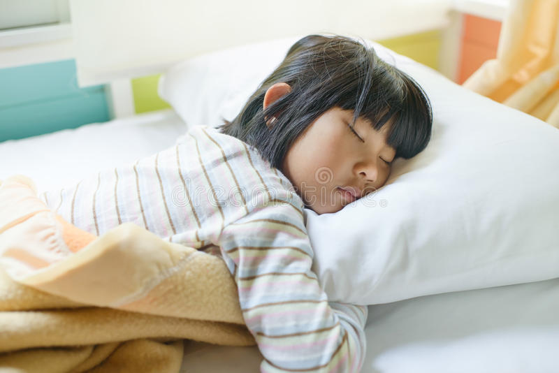 Asiatisches Mädchen, das auf dem Bett bedeckt mit Decke schläft stockfotos