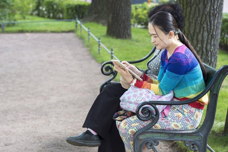 Asiatisches Mädchen, das auf einer Parkbank am Eingang zum Einsiedlerei-Museum von St Petersburg, Russland, im September 2018 sit lizenzfreie stockfotos